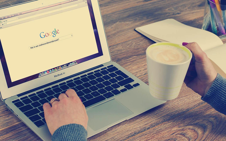 Laptop met vraag in Google 'Wat is een zoekwoordenonderzoek?' en twee handen met een cappuccino